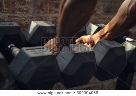 Hand of african man taking heavy dumbbell out of set of black weights. Closeup hands of black bodybuilder pick dumbbell to exercise. Hands of muscular guy taking dumbbell for strength training.