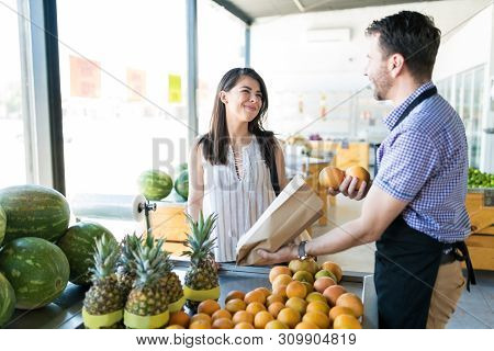 Male Grocery Owner Packing Oranges In Paperbag While Talking To Female Customer At Fruit Stall In Or