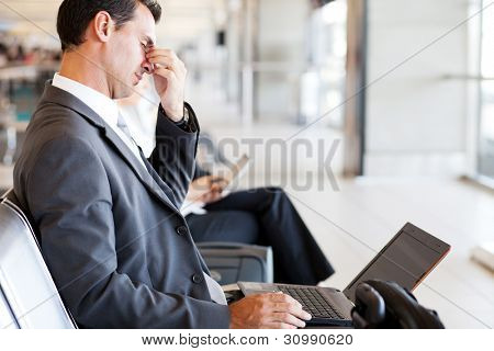 tired businessman taking a break at airport