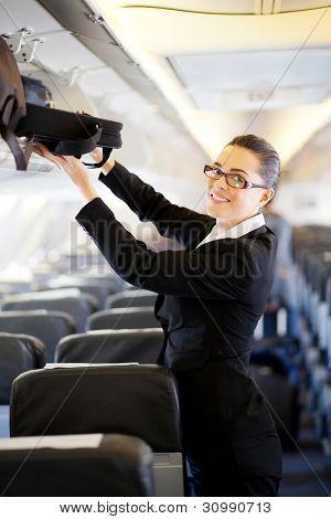 pretty businesswoman putting her luggage into overhead locker on airplane