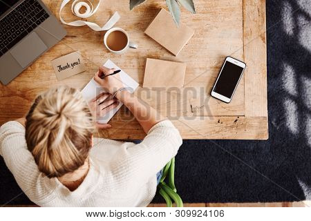 Overhead Shot Looking Down On Woman Writing In Generic Thank You Card