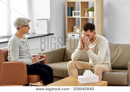 psychology, mental therapy and problem concept - senior woman psychologist taking notes to notebook and sad young man patient at psychotherapy session