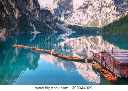 Wooden boats in a row on summer morning at Lago di Braies (also known as Pragser Wildsee) in Dolomites Mountains, Sudtirol, Italy.
