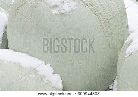 Close-up Of Silage Balls In Winter Covered With Snow