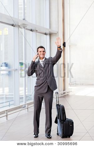 young businessman waving good bye at airport poster