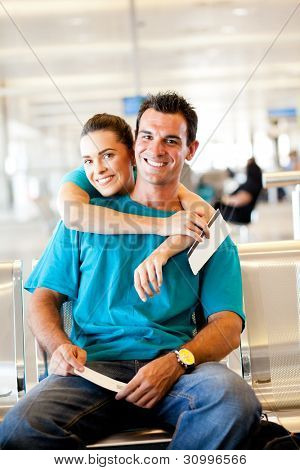 happy young couple waiting for their flight at airport