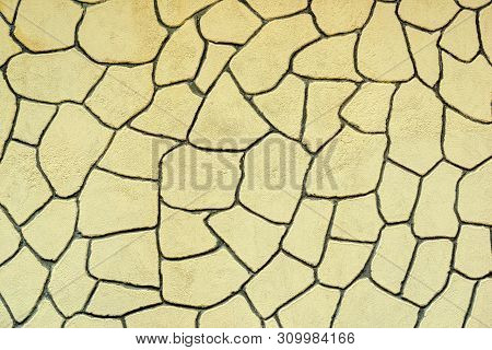 The Plastered Wall With An Abstract Mesh Mosaic Pattern Of Monotonous Yellow Color For The Textured