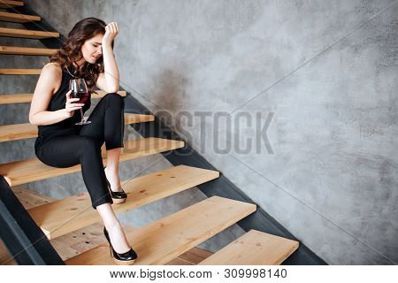 Young Woman Has Problems With Alcohol. Sitting On Steps Alone. Having Hangover. Holding Glass Of Red