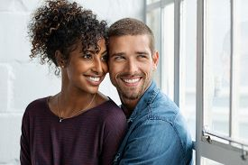 Loving multiethnic couple embracing and sitting near window. Happy girlfriend and smiling boyfriend looking away and thinking about their future together. Young man and african woman contemplating.