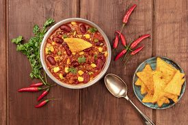 Chili Con Carne With Ingredients, Cilantro, Oregano, Chili Peppers, And Nachos, Shot From The Top On
