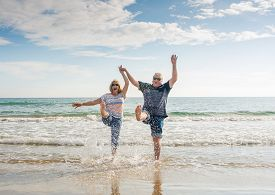 Senior Couple In Love Walking On The Beach Having Fun In A Sunny Day