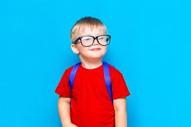 Happy Smiling Boy In Red T-shirt In Glasses Is Going To School For The First Time. Child With School