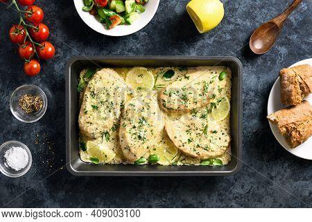 Chicken Or Turkey Breast In Creamy Garlic Sauce In Baking Dish Over Blue Stone Background. Healthy D