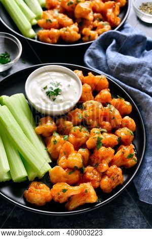 Close Up View Of Cauliflower Buffalo Wings With Celery And Sauce. Healthy Eating, Plant Based Food C