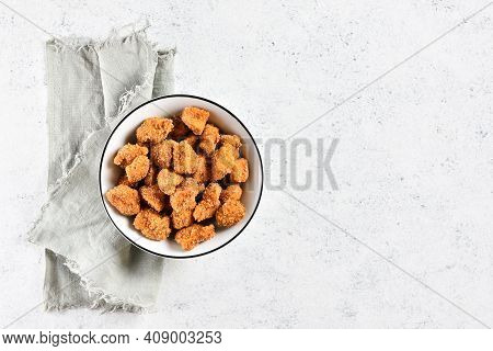 Crispy Fried Breaded Chicken Bites In Bowl Over Light Stone Background With Free Text Space. Tasty C