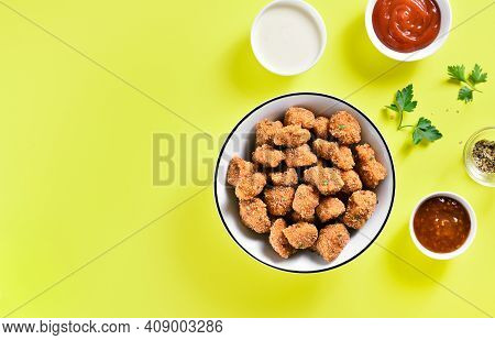 Crispy Fried Breaded Chicken Bites In Bowl Over Yellow Background With Copy Space. Tasty Chicken Nug