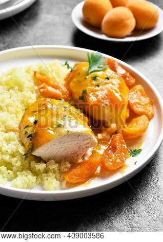 Close Up View Of Chicken Breasts In Apricot Sauce And Couscous On Plate Over Stone Background. Tasty
