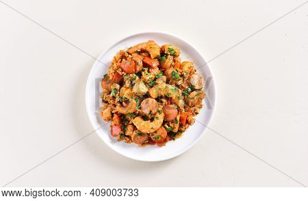 Creole Jambalaya With Prawn, Chicken Meat, Smoked Sausages And Vegetables On Plate Over Light Backgr