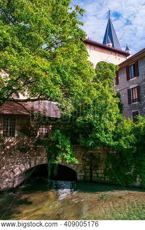 A Building On A Canal Bridge In The City Centre Of Annecy, France Near Jardin De L'eveche With Eglis