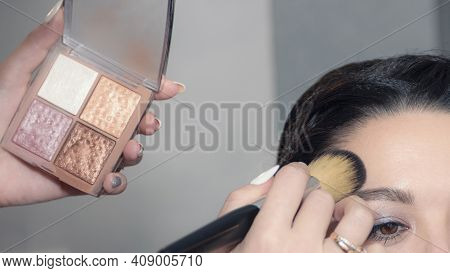 A Make-up Artist Makes Makeup For A Young Woman With Long Eyelashes And A Delicate Natural Complexio