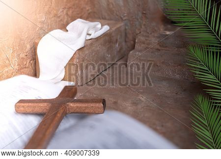 Palm Leaves On A Empty Tomb And Wooden Cross Over Open Bible Background With Copy Space For Inscript