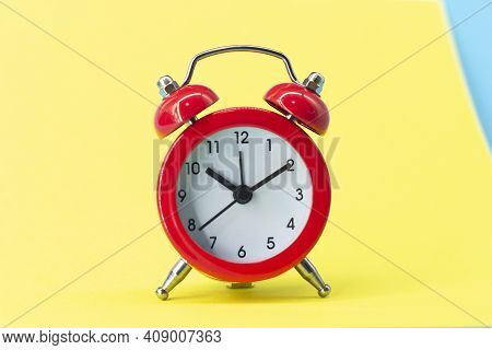 Red Round Analog Alarm Clock Isolated On Yellow Background. Time 10:10.