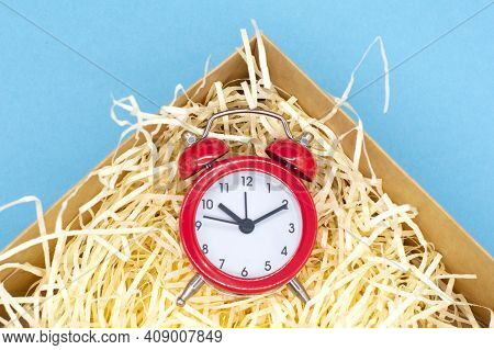 Red Round Analog Alarm Clock In A Box On A Blue Background. Time 10:10. Space For Text.