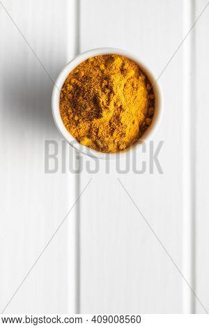 Indian turmeric powder. Turmeric spice. Ground turmeric in bowl. Top view.