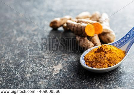 Indian turmeric powder and root. Turmeric spice. Ground turmeric in ceramic spoon.