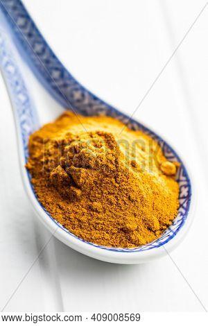 Indian turmeric powder. Turmeric spice. Ground turmeric in ceramic spoon.