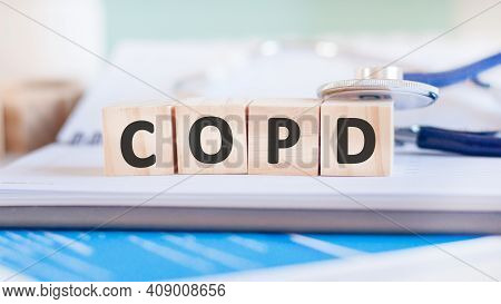 The Word Copd Is Written On Wooden Cubes Near A Stethoscope On A Paper Background. Medical Concept.