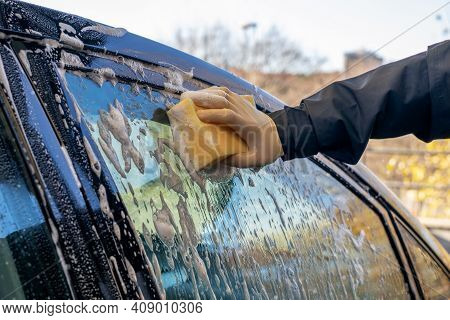Car Window Washing With A Soapy Sponge.male Hand Holding Soapy Sponge.  Outdoor Activity And Taking