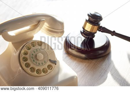 Old White Phone And Law Hammer. Concept Of Legal Advice, Consultation, Counseling Over The Phone.