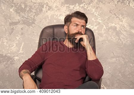 Thinking On Serious Problem. Serious Hipster Relax In Chair. Serious Look Of Bearded Man. Solving Pr