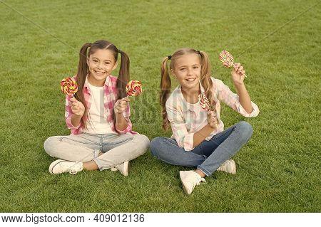 Enjoy These Lollipops With Taste Sensation. Happy Children Hold Lollipops Green Grass. Eating Large