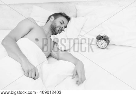Man Sleeping Bed White Bedclothes And Red Alarm Clock, Deep Sleep Concept.