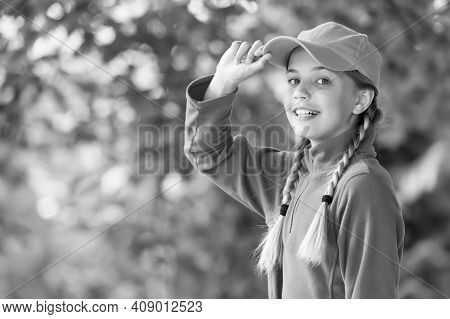 Her Style Is A Lot More Casual. Happy Child In Casual Style Natural Outdoors. Little Girl Wear Baseb