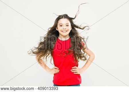 Interested In My Hair And My Hairdresser. Happy Small Girl Child Smiling With Flowing Long Brunette