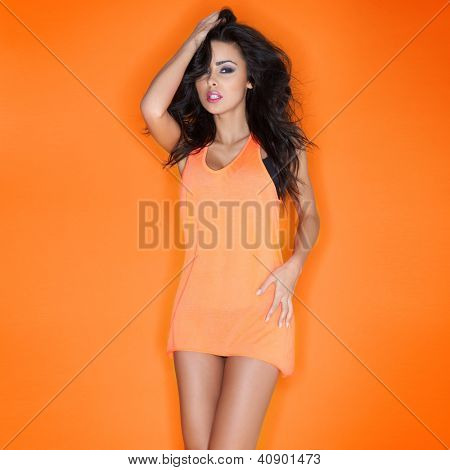 Beautiful sultry brunette in a skimpy miniskirt posing with her hand to her long tousled hair, three quarter studio portrait on orange