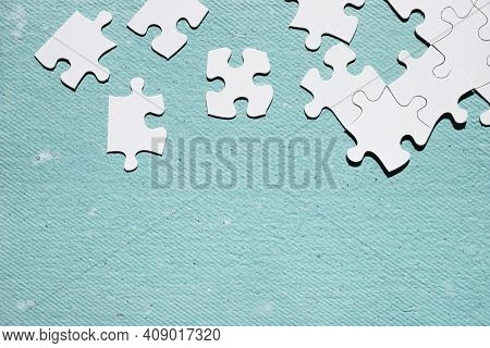 A Close Up Of Puzzle Pieces. White Jigsaw Puzzle Piece Blue Textured Surface