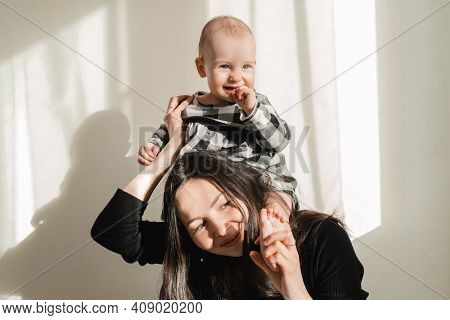 Mom Holds The Baby On The Neck. Daughter Plays With Her Mom. Have Fun With Your Parents
