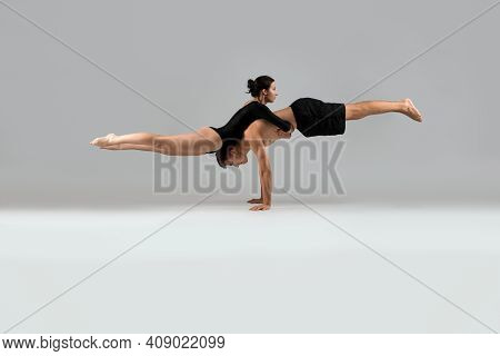 Couple In Sportswear Doing Balance Exercise On Hands