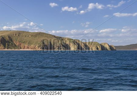 View From The Japanese Sea Of Beautiful Rugged Cliffs Of Popovs Island On Sunny Day