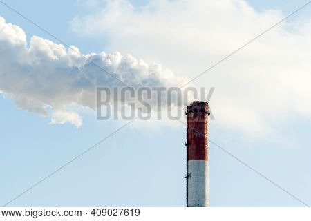 Smoke From Industrial Pipes Close Up. Against The Blue Sky. Space For Text