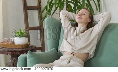 Tired Young Woman Is Resting In A Comfortable Chair With Her Hands Behind Her Head