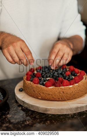 Male's Hands Decorating A Homemade Cheesecake With Fresh Raspberry And Blueberry. Man Cooking A Cake