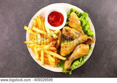 grilled chicken leg,  french fries and ketchup