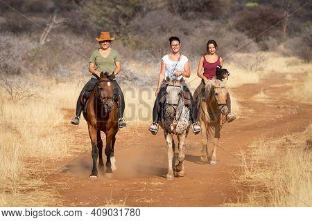 Three Women Ride Horses On Dirt Track