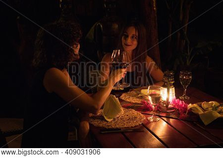 Two Brunettes Clinking Glasses At Dinner Table