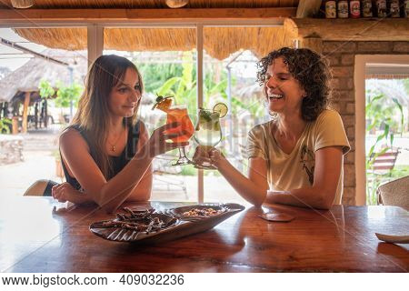 Two Brunettes Toast Each Other At Bar